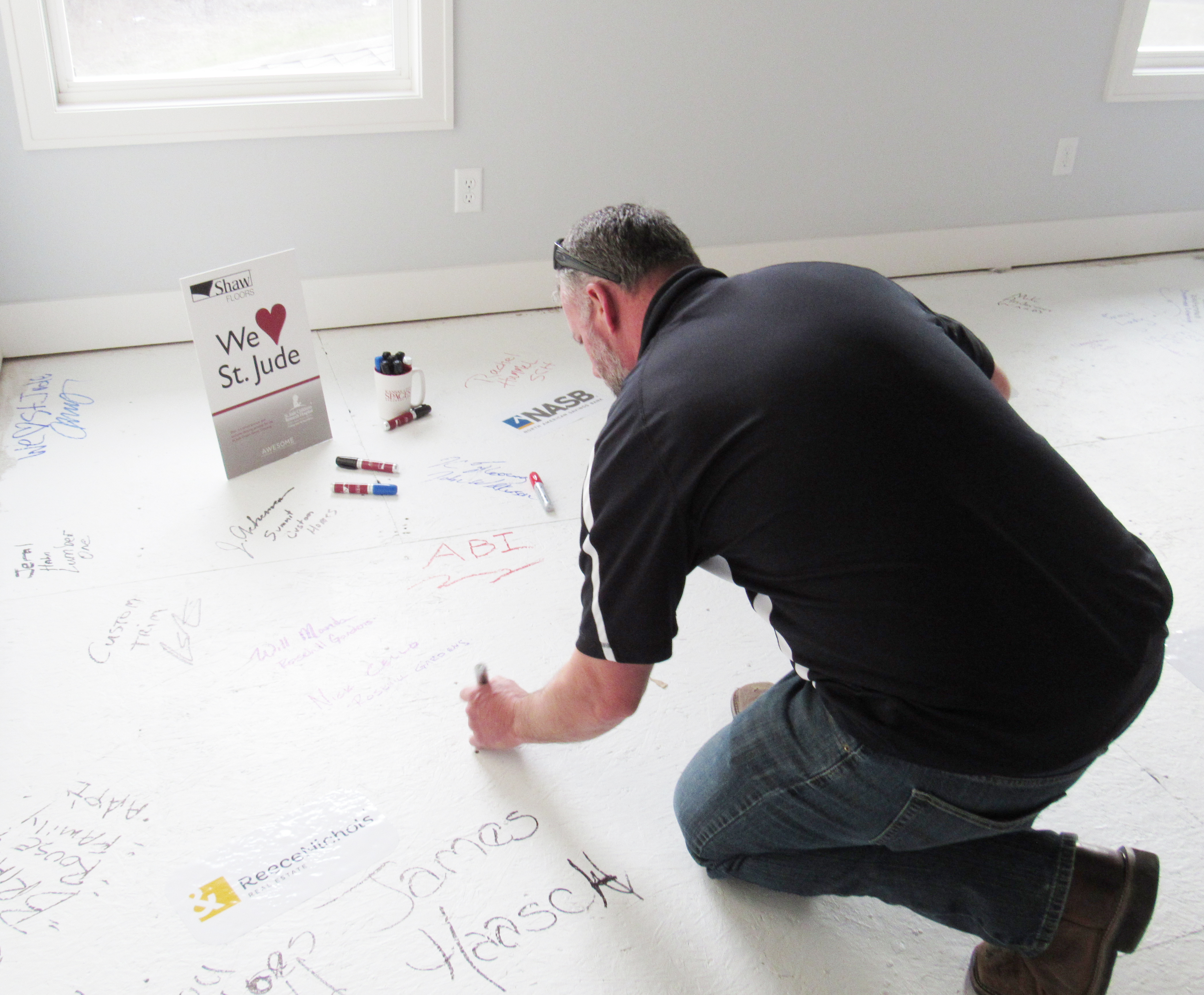 Sales Manager Mike signs his name on the unfinished flooring, along with a collection of other names already written