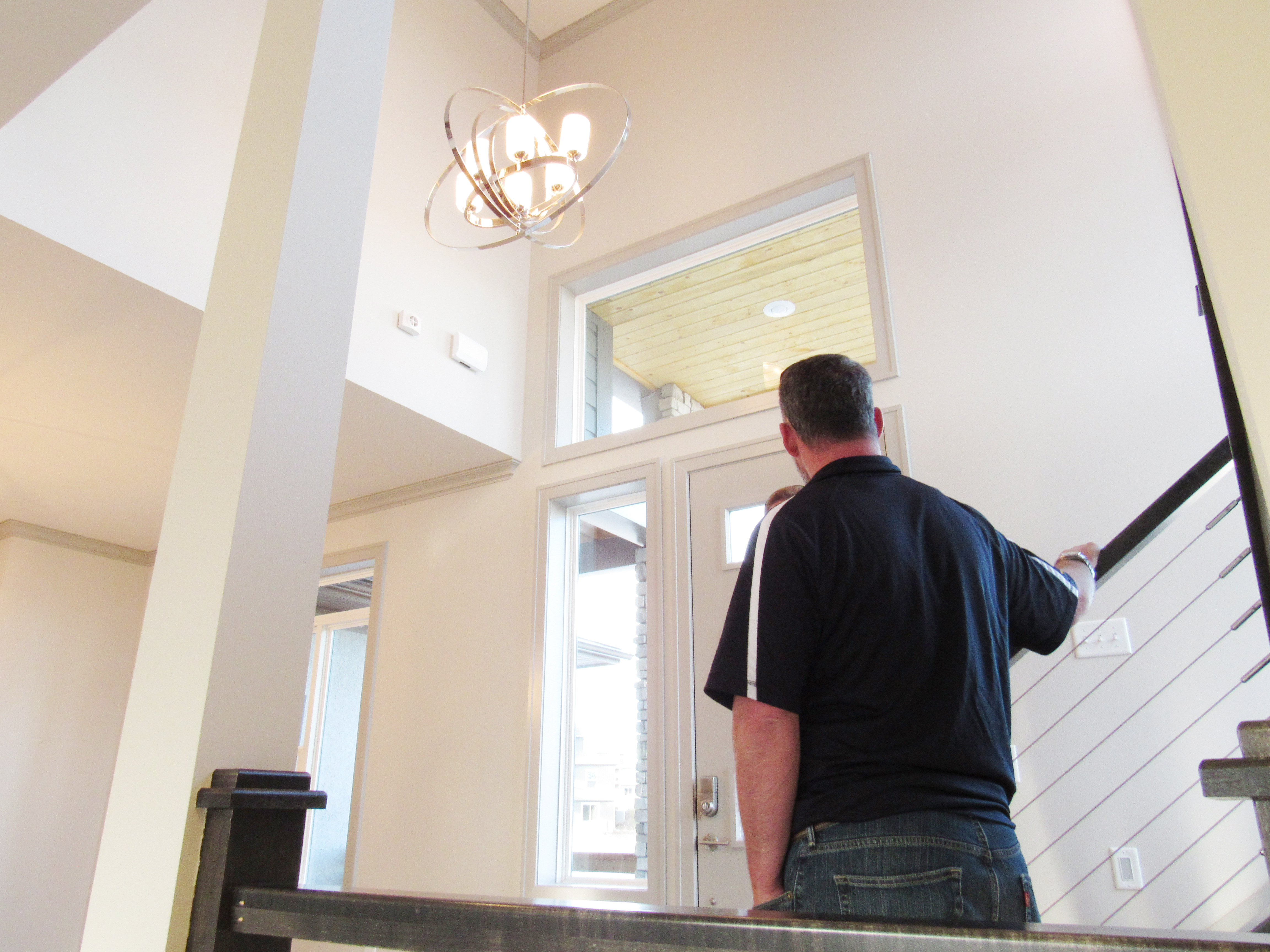 Sales Manager Mike is talking to a person, while standing in the elegant foyer of the Dream Home